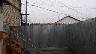 Fences and barbed wire surrounding the visitors entrance to the Sadovaya Colony. (Photo: Charles Digges)