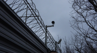 Tkachev's fence outfitted with new video cameras. (Photo: Bellona/EWNC/Greenpeace)